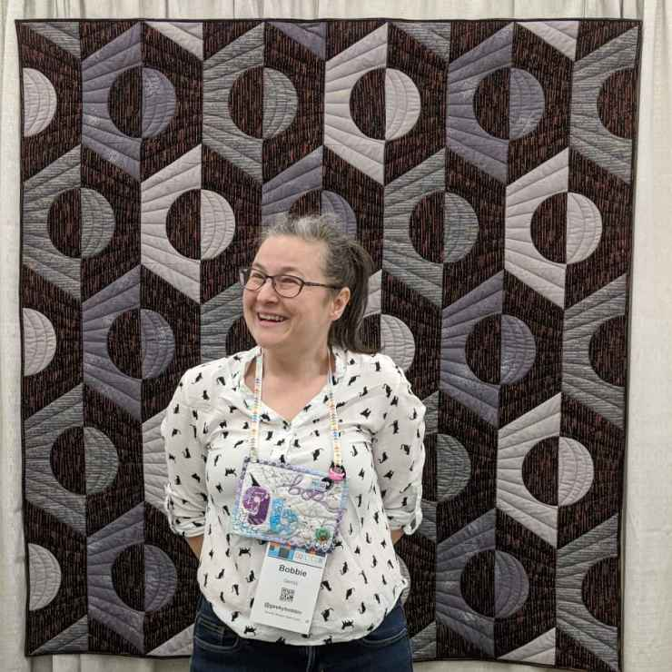 Bobbie Gentili aka the Geeky Bobbin with her Riveting quilt at QuiltCon 2020. QuiltCon is the biggest modern quilting event of its kind.