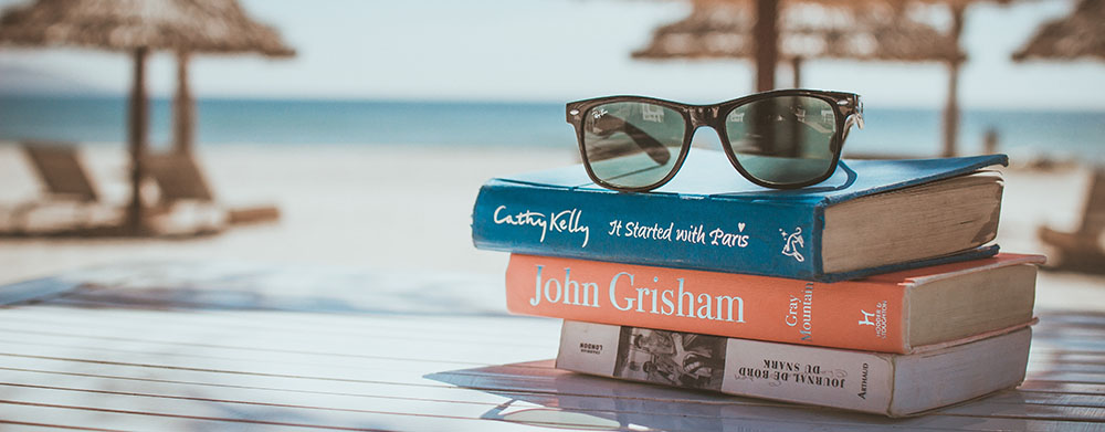 books stacked on a table, sunglasses on top, and a beach in the background out of focus