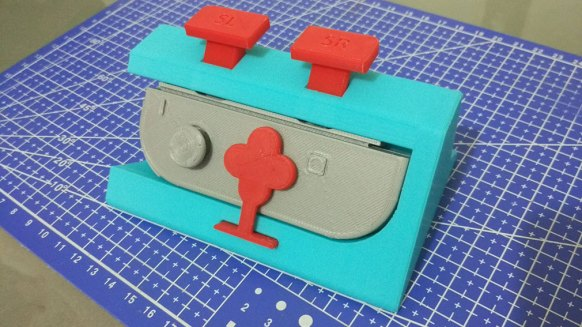 A blue 3D printed case surrounding a printed, gray controller. There are two red buttons on top for the left and right controls.