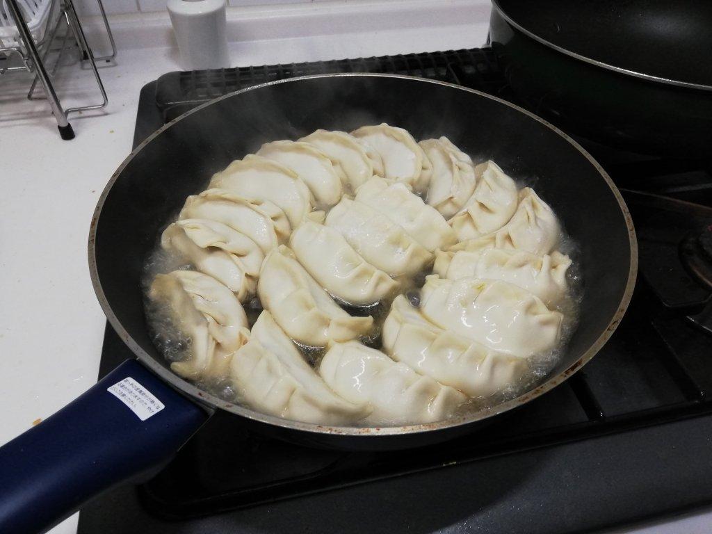 フライパンに水を入れて餃子を蒸し焼きにする