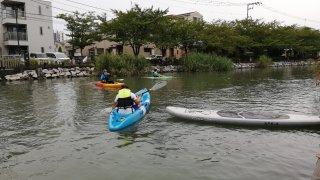 新川でカヤック体験をする人たち