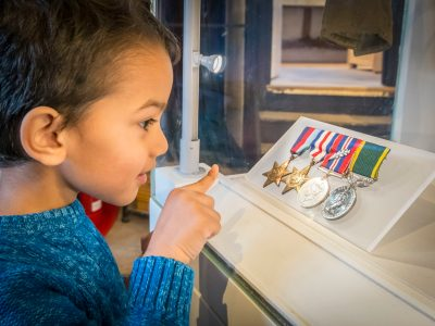 A young boy looking attentively at world war two medals.