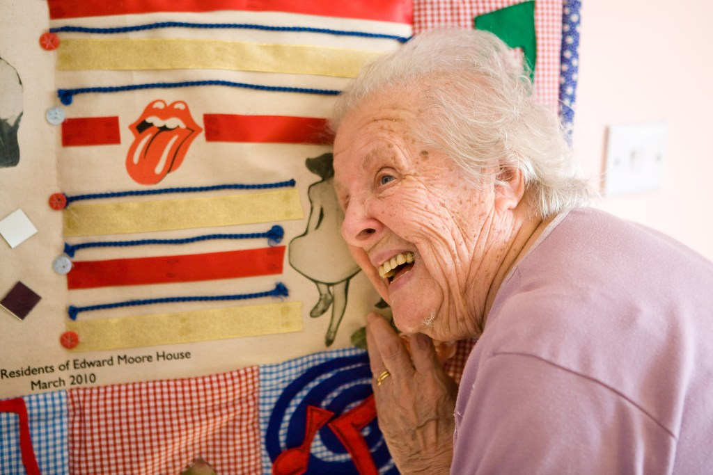 An older woman interacting with a story quilt.