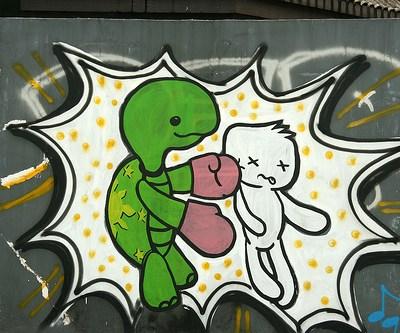 graffiti of a turtle punching someone