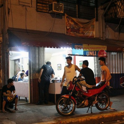 people hanging by a corner store at night