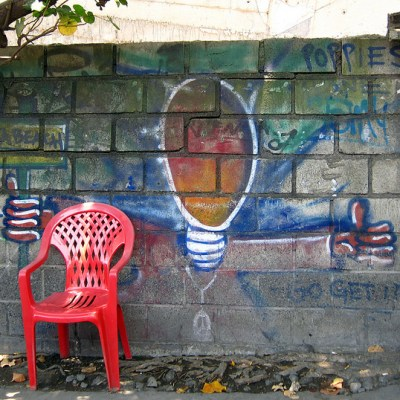 red plastic monobloc chair in front of graffiti