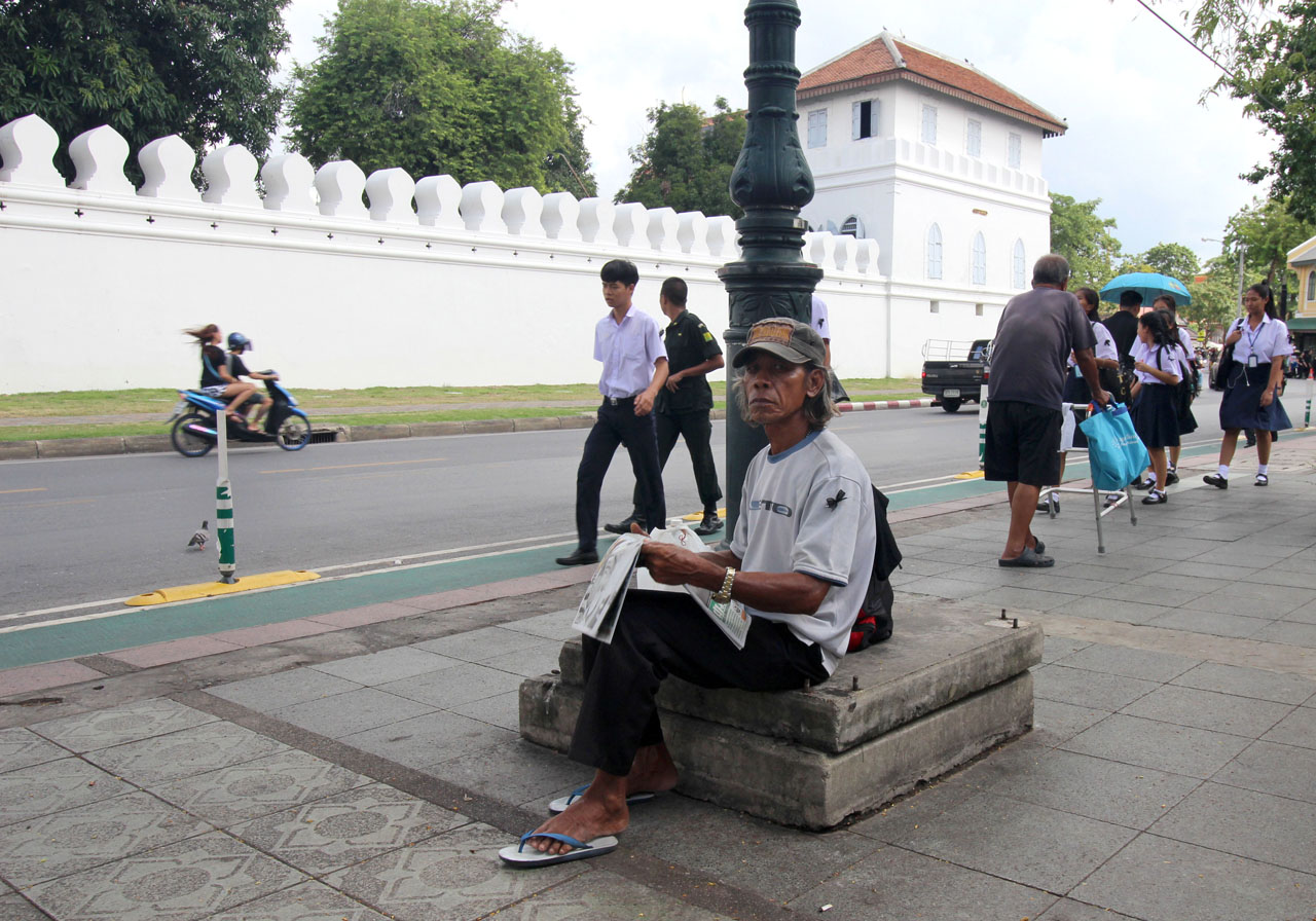man holding a newspaper in front of the Grand Palace