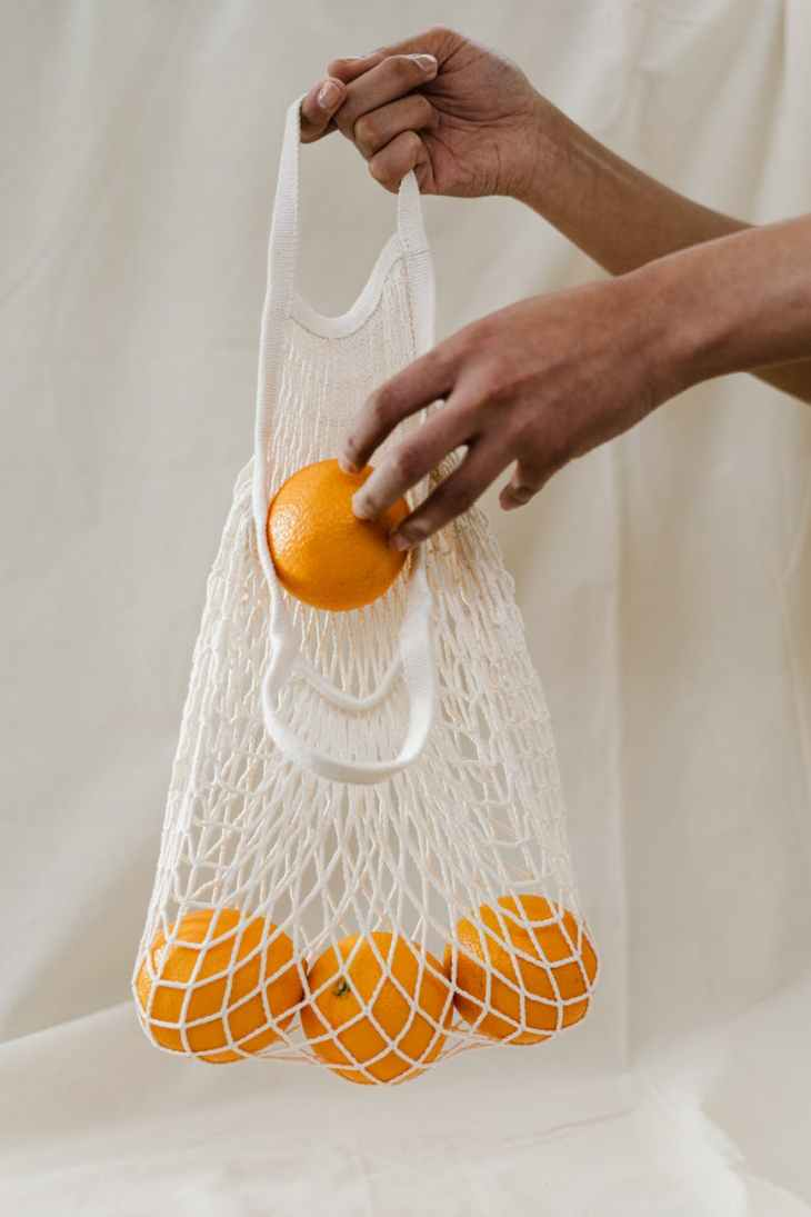 A string bag filled with oranges