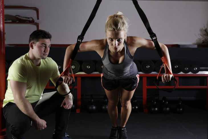 A woman using a arm machine at the gym with a male trainer