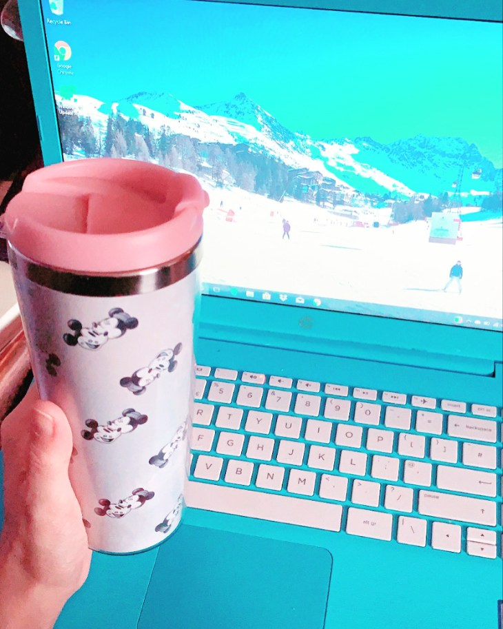 A Disney flask with mickey and minnie mouse in front of a blue laptop with a ski background.