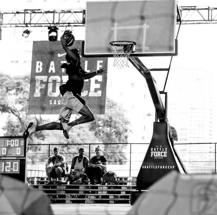 A black and white photo of a woman about to dunk a basketball.