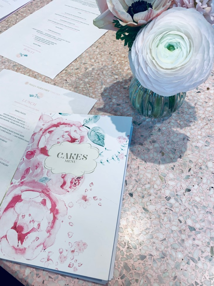 """Inside the London, Chelsea """"Peggy Porschen"""" cafe/bakery showing the menu and flowers on the table."""
