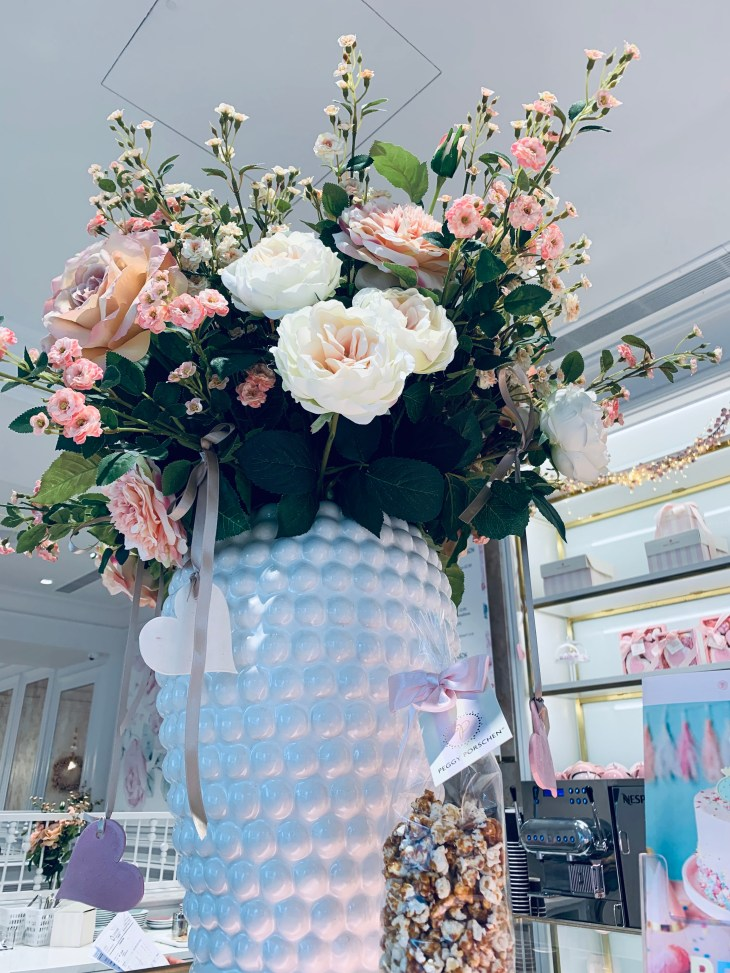 """Giant bouquet of pink and white flowers in a white vase, inside the """"Peggy Porschen"""" cafe London."""