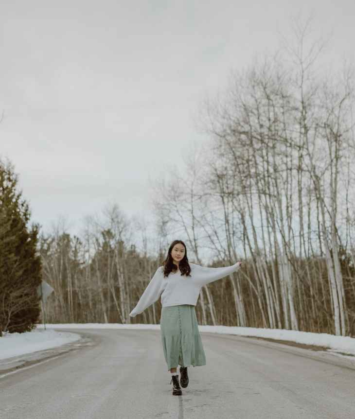 content young ethnic woman strolling on asphalt road among bare trees