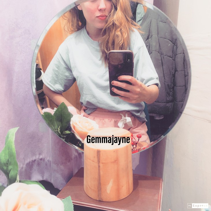 """A purple background with a small mirror in the middle. In the mirror is a woman taking a selfie. The woman is wearing a blue top, with pink shorts and only showing half of face. Text at the bottom of of mirror selfie says """"Gemmajayne""""."""