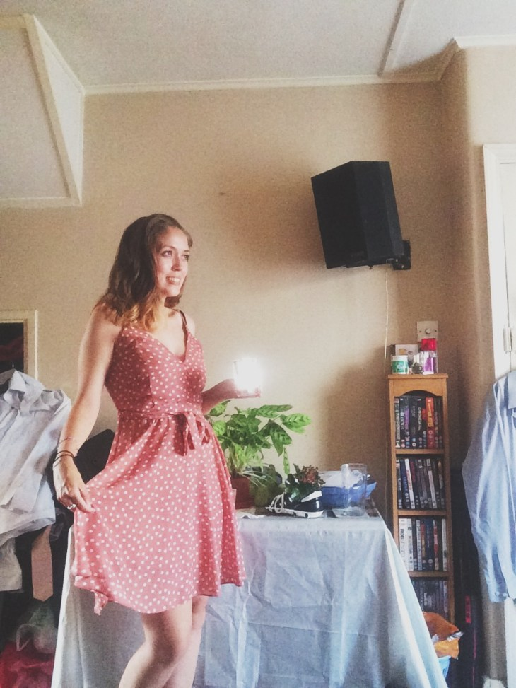 A woman wearing a pink polka dot summer dress standing in the living room with a table that has a big green plant on it.