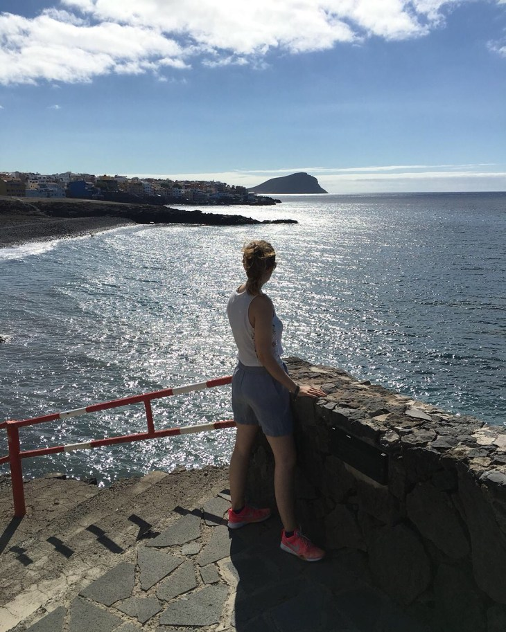 A woman wearing shorts and a short sleeve top standing on a cliff side with the view of the sun and sea, and mountains in Tenerife.