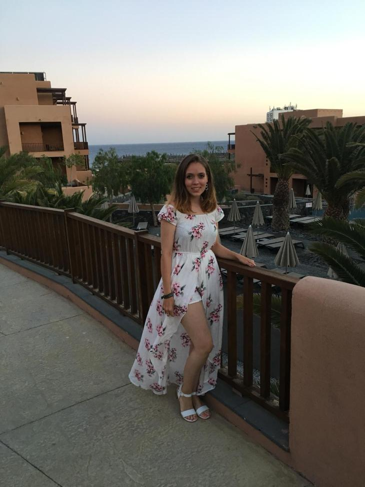 A woman standing in a hotel resort in Tenerife with the views of apartments and the sea in the background, whilst wearing a long white dress with flowers all over it.