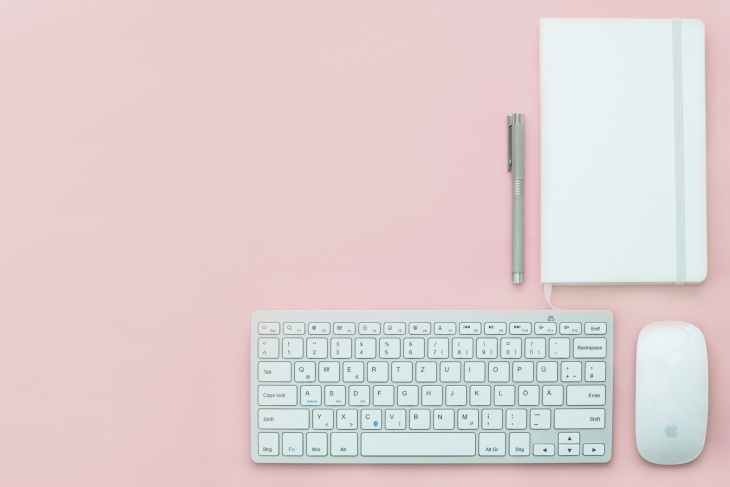 A pink background with a white keyboard and mouse, a white notebook and pen.