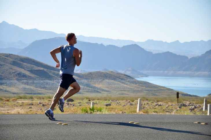 A man running on road with the mountains in the background, to improve your running.