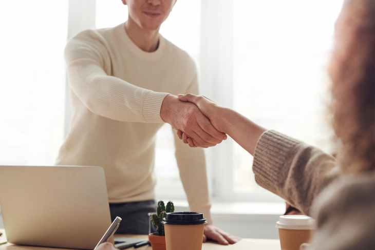 Someone shaking the hand of someone else in a blurry pic over a table that has a laptop and a couple of drinks on it.