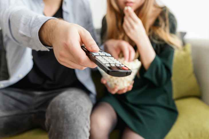 A blurry picture of a man holding a controller pointing it at the TV, next to a woman holding a bowl of popcorn.