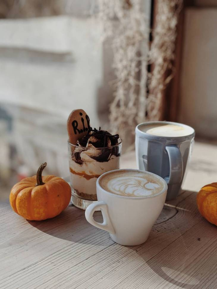 two small orange pumpkins next to a chocolate dessert and two coffee drinks in mugs.