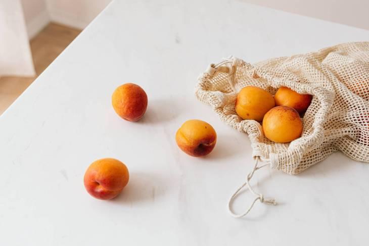 a selection of peaches in a reusable bag.