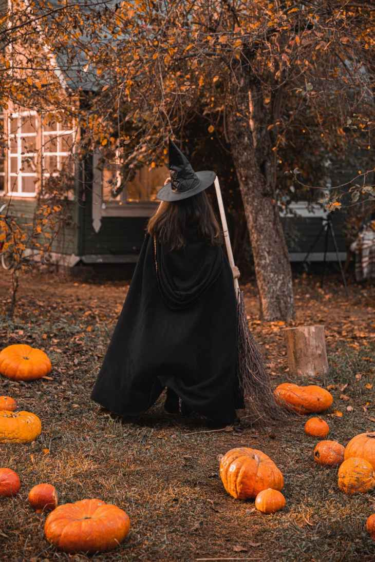 A woman dressed in a witches outfit for Halloween holding a broomstick and standing facing away from the camera outdoors in a filed with pumpkins.