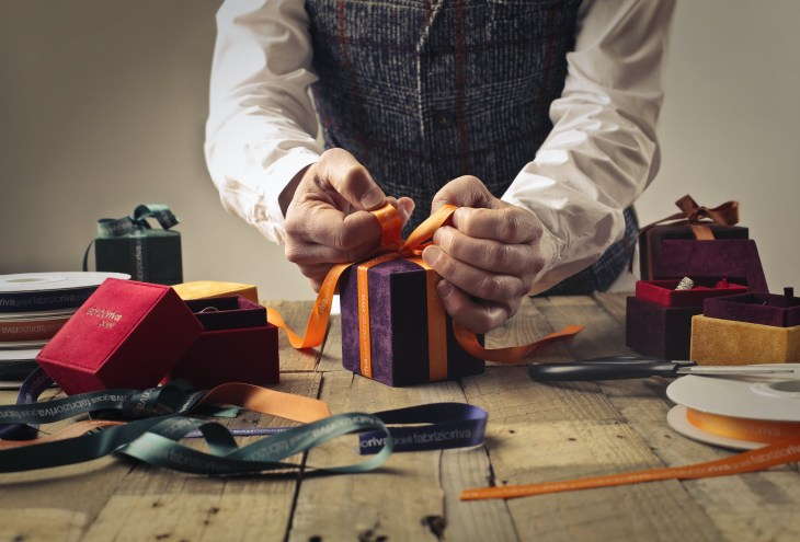 Some hands wrapping up a present and tying a bow around it.