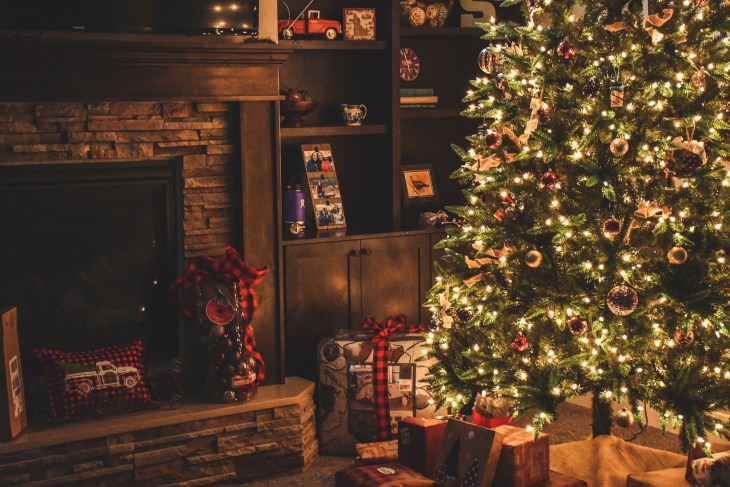 A lit up Christmas tree with presents underneath in a living room at night