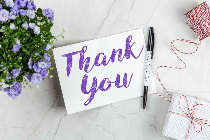 "A pad with ""thank you"" on it in purple writing and a pen, next to a present with string and blue flowers."