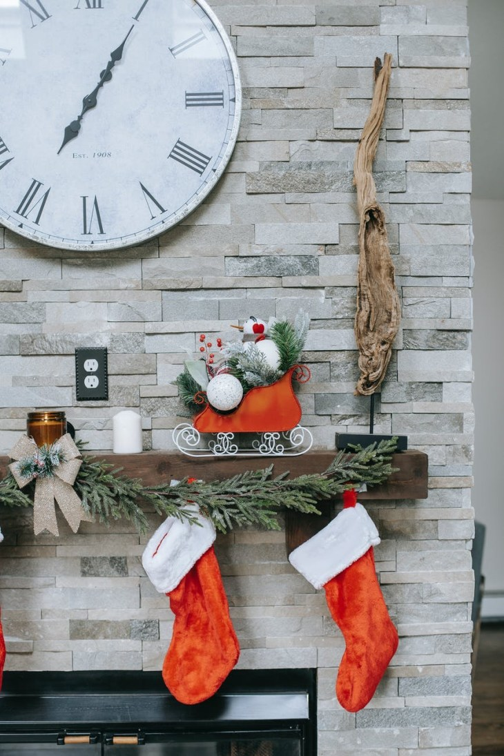 A couple of red and white Christmas stockings hanging on a fireplace. With a Santa sleigh decoration on the mantle piece