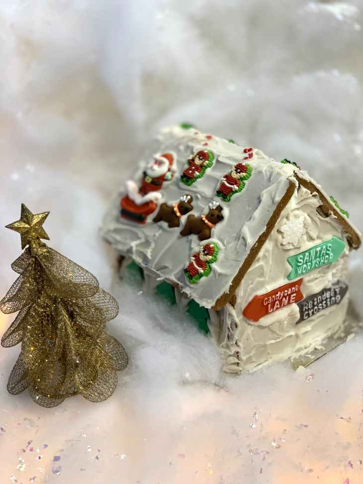 """A decorated gingerbread house full of icing, edible signs """"candycane lane"""", """"reindeer crossing"""" and """"santas workshop"""" and reindeer, santa and elf decorations. Next to a golden sparkly Christmas tree and on fake snow."""