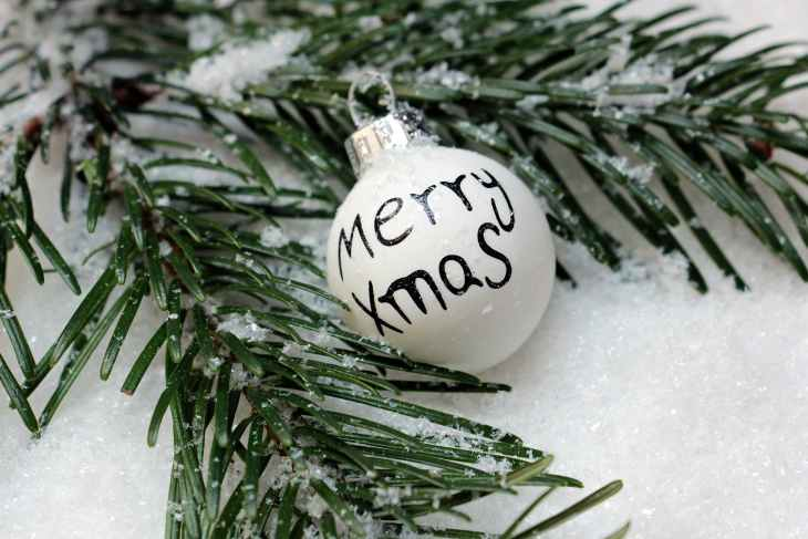 "A selection of white snow, with some Christmas tree branches laying in it and a white Christmas Bauble with ""Merry Xmas"" on it in black writing."