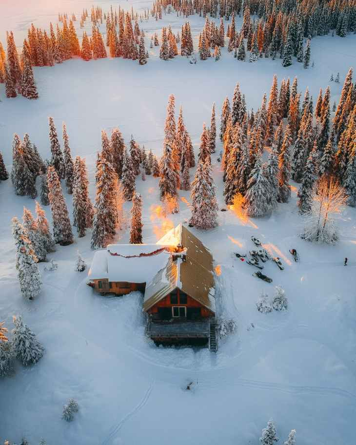 A birds eye view of a cabin in the snow and woods, surrounded by snow filled trees.