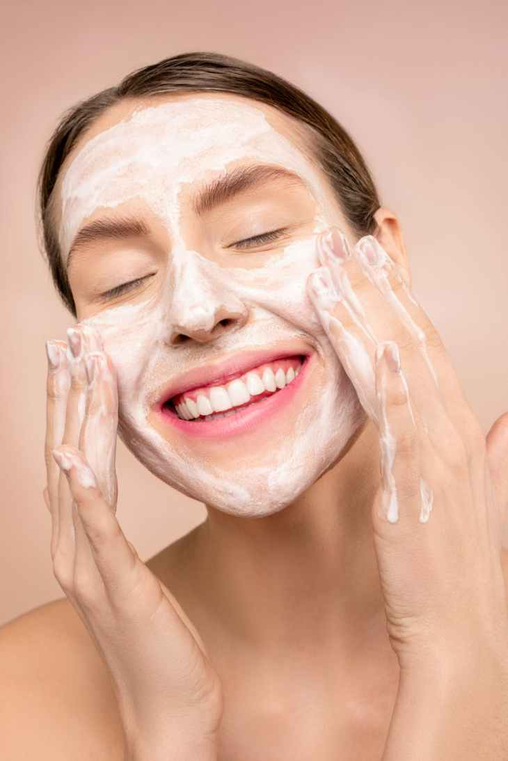 A woman smiling with her eyes closed whilst she applies a white face cream to her skin with her hands.