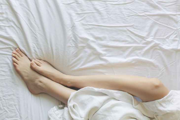 Some legs in a bed wrapped up in a sheet, looking after their well-being.