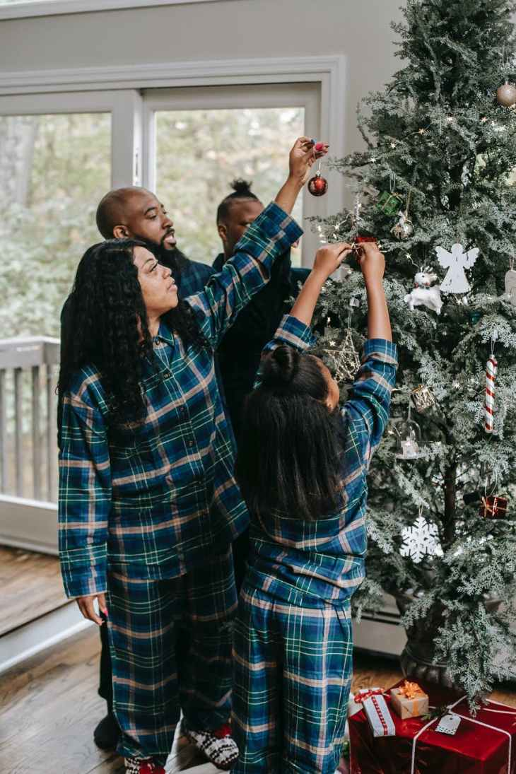 A family wearing matching Pyjama's all hanging decorations on the Christmas tree.