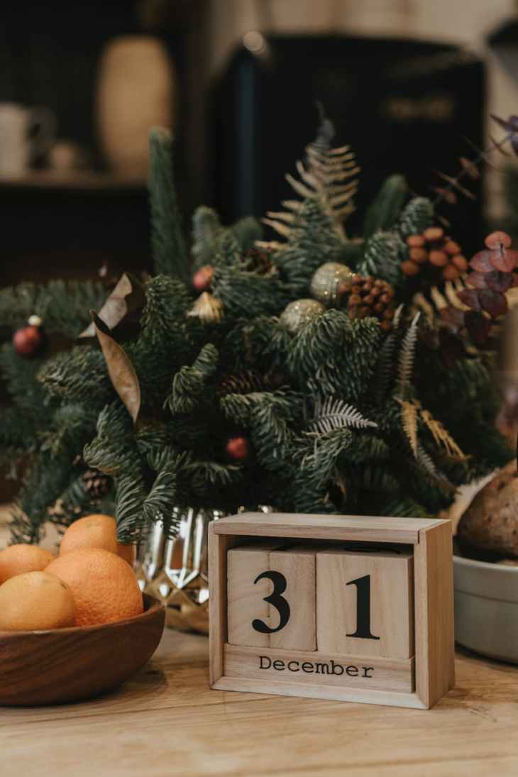"A christmas tree bowl with a wooden sign that says ""31 December"" on it that you can change, next to a bowl of oranges in front of the Christmas tree bowl."