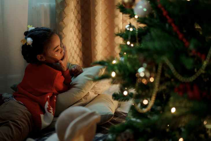 A young girl laying down on the floor on a pile of pillows looking in the distance, next to a Christmas tree.
