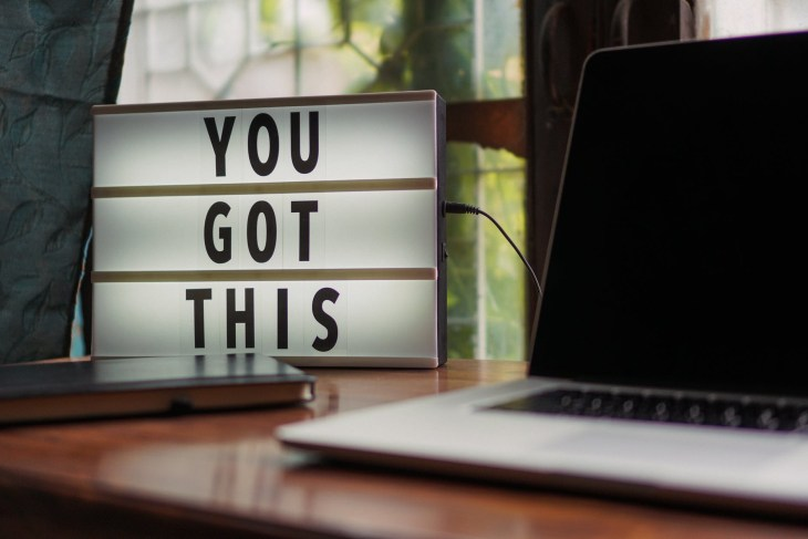 """A large light up sign that says """"you got this""""  on it next to a silver laptop that is open and a phone all placed on a desk."""