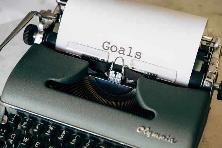 "A silver/grey type writer with ""goals"" written on the parchment paper in the type writer."