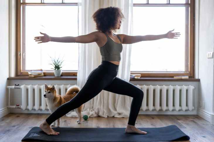 A woman standing with one leg forward bent, arms out (one behind and one in front) facing forwards on a yoga matt completing a morning workout in front of two huge windows.