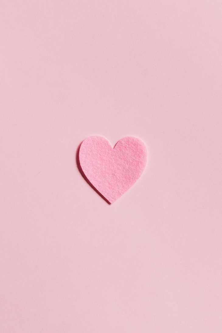 A pink background with a small pink felt heart in the middle