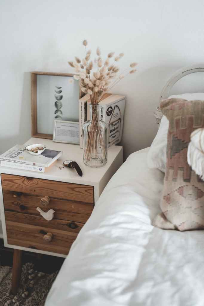 cozy light interior of comfy bed and bedside table for a spring cleaning