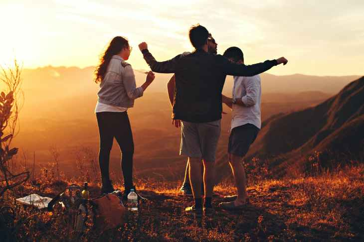 four person standing at top of grassy mountain, to enjoy life outside of work.