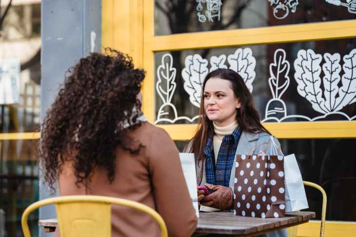 girlfriends speaking at table near shopping packages in street cafe