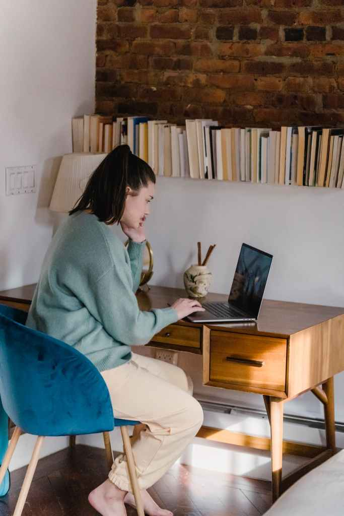 young woman working on laptop in cozy apartment