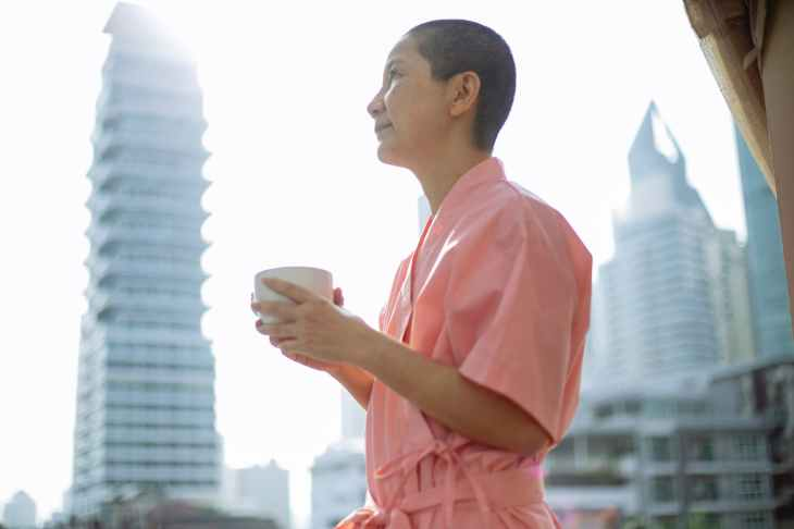 short haired happy asian woman with breast cancer enjoying tea